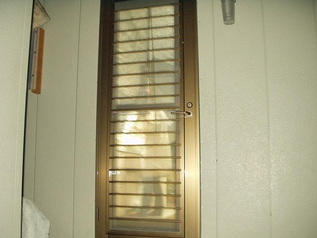 夜に屋外から見たアルミ製の勝手口ドア