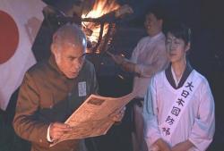 黒川を賞賛した新聞を読んでいる村長