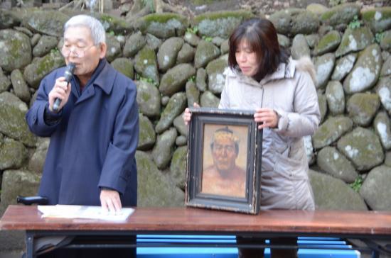 力士 大嶌傳吉の解説をする郷土史家の樋口秀司さんと伝吉肖像画(油絵6号)を抱く末裔の方