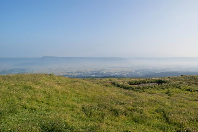 緑の山肌越しに阿蘇の麓を眺める
