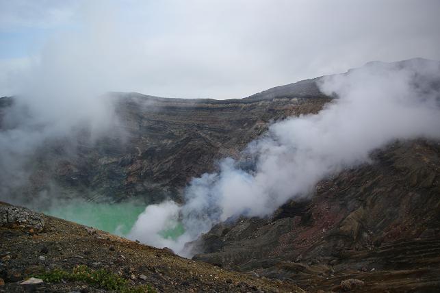カルデラの岩肌に沿って蒸気が昇る