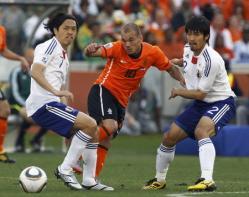 阿部勇樹と遠藤保仁に挟まれながらパスを出すオランダのW・スナイダー。