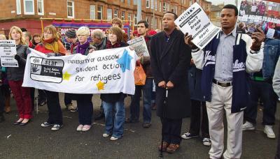 デモ行進 横断幕 人々 訴える