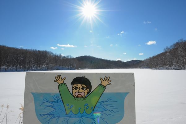 凍結した池と危険を知らせるイラスト。全国に多量にあるであろうこの手のヘタ絵(失礼)は平凡な公務員の手によるものなのか?