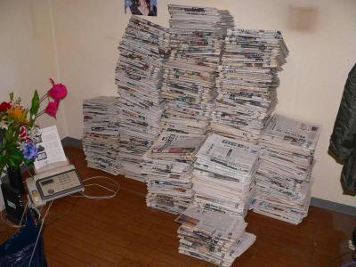 写真キャプション=引越し前の部屋に積み上げられた目を通してない新聞の山